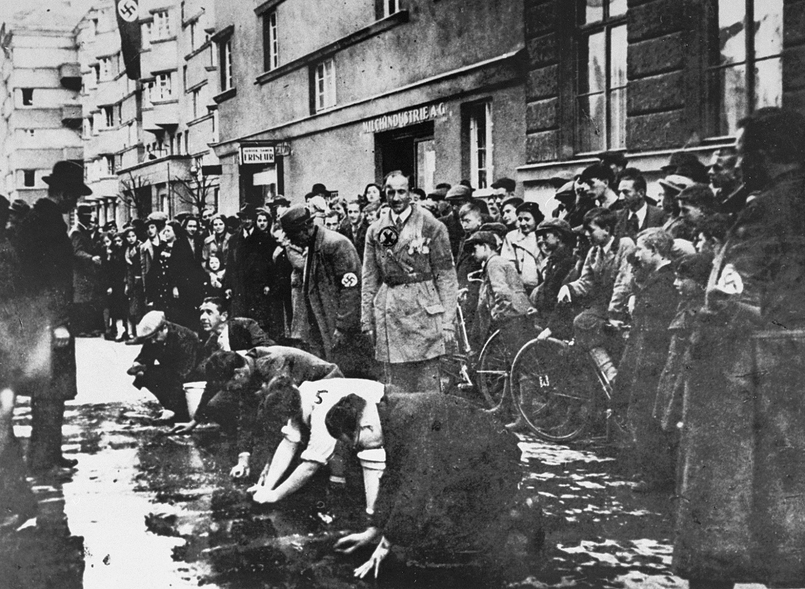 In this image, as part of a ritual of public humiliation, Jewish men and women were forced to scrub the streets to remove political slogans that were critical of Germany's annexation of Austria.